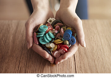 Hands full of colorful buttons