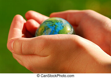 Hands globe - Child\\\'s hands holding a globe on green...