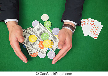 Hands grabbing dollars and chips from table beside royal...