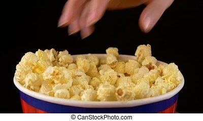 Hands grabbing popcorn on black, slow motion - Hands...
