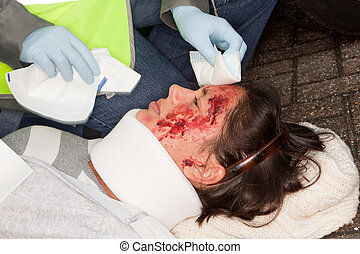 Woman with wounded face being helped by a paramedic