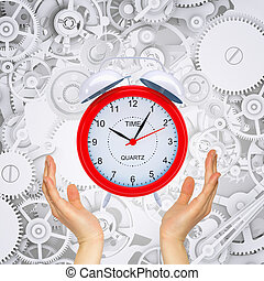 Hands hold alarm clock with gears. Conceptual background