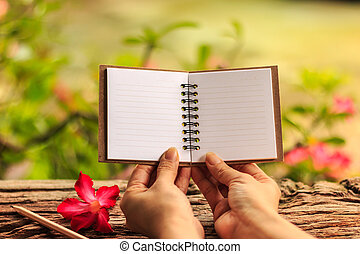 Hands hold blank note book