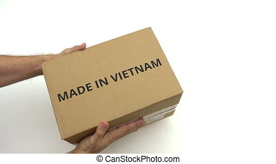 Hands hold carton with MADE IN VIETNAM text - Man holds...