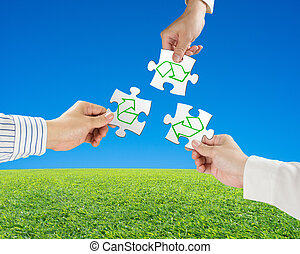 Hands hold puzzles with recycle symbol and beautiful landscape green meadow, clear blue sky background