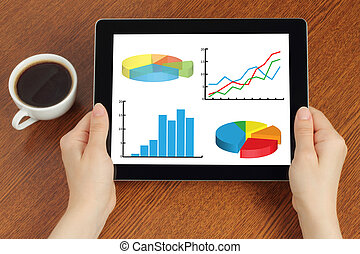 Hands hold tablet PC with graphs on wooden background