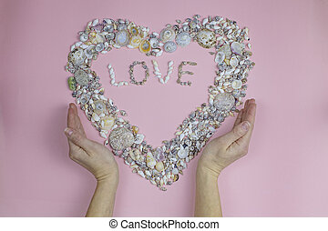 Hands hold the word love and a heart lined with seashells