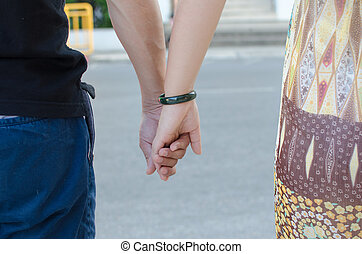 two pairs of hands in love tenderly hold together.