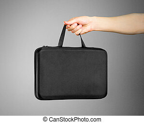 Hands holding a black case. Isolated on grey background