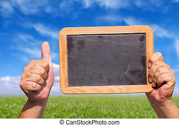 Hands holding a blank slate blackboard in the air