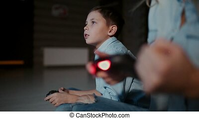 Hands holding a controller to a game console, and in the background the boy looks at the faucet and playing video games. The focus shifts from one to another.