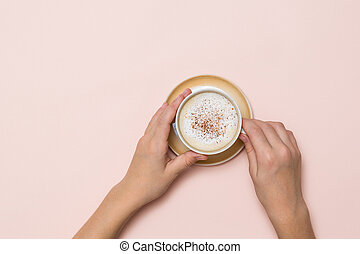 Hands holding a Cup of coffee with cream and cinnamon on a light background.