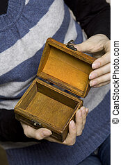 Hands holding a decorative wooden box