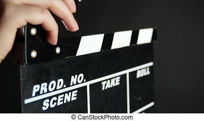 Hands holding a film clapper board, on black, close up -...