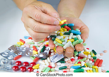 Hands holding a lot of pills