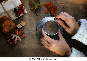 hands holding a mug of hot coffee on a table