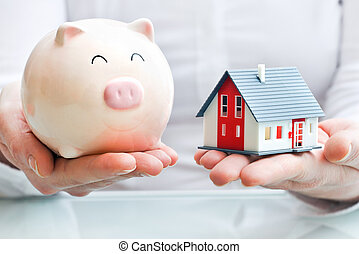 Hands holding a piggy bank and a house model. Housing...