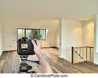 Hands holding a professional camera on tripod