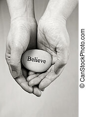 Hands holding a rock with engraved word Believe