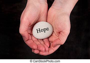 Hope - Hands holding a rock with engraved word Hope