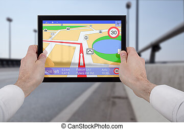 hands holding a touchpad pc, using the navigation programme