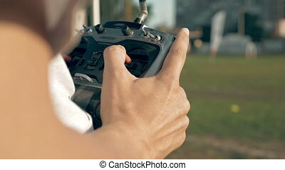Hands holding a transmitter controlling FPV drone - Close up...