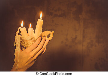 Hands holding a wax candle.
