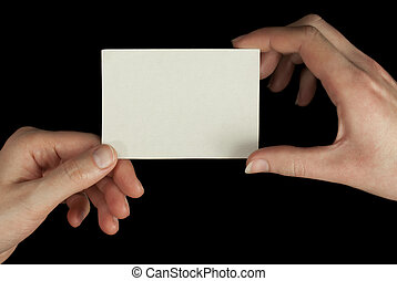 Hands holding a white card isolated on black background