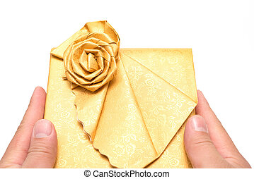 hands holding a wrapped golden present box on white background