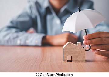 Hands holding an umbrella on a wooden house. Concept of home insurance, home care and safety.