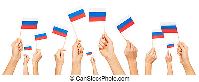 Hands holding and raising small flags of Russia