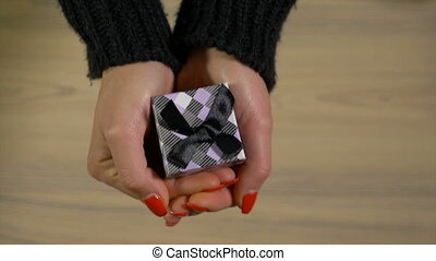 Hands holding and showing a small gift box