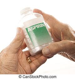 Hands holding aspirin bottle. - Close-up of elderly male...