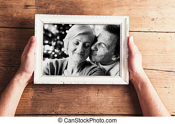 Hands holding black-and-white photo of senior couple in picture