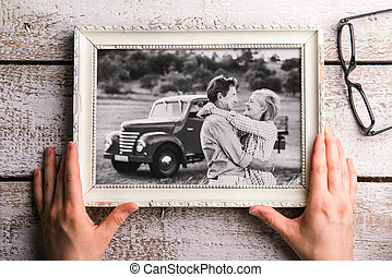 Hands holding black-and-white photo of seniors in picture frame
