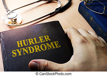Hands holding book Hurler syndrome.