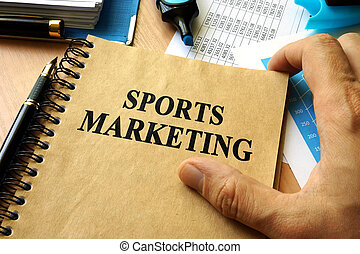 Hands holding book with title sports marketing.