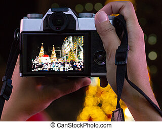 Hands holding camera take photo of Christmas tree, Santa Claus and crowed people celebrating Christmas and new year.