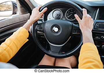 Hands holding car wheel and driving - Close up of female...
