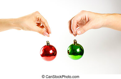 Hands holding Christmas ball. On the background of many Christmas balls. Lot Christmas tree decorations. Colored glass balls. Isolated on a white background