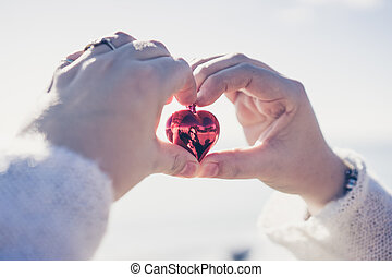 Hands holding Christmas heart against of cloudy sky
