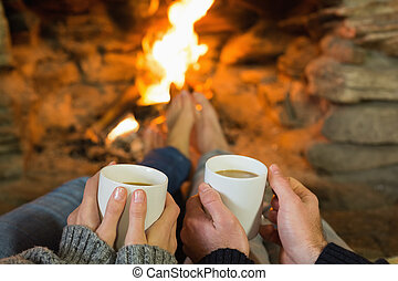 Hands holding coffee cups in front of lit fireplace -...