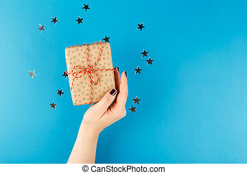 Hands holding craft paper gift box