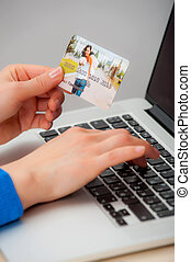 Hands holding credit card and using laptop.