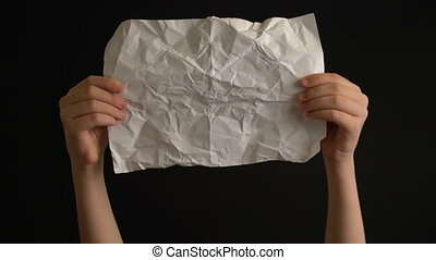 Hand's holding crumpled paper on black background