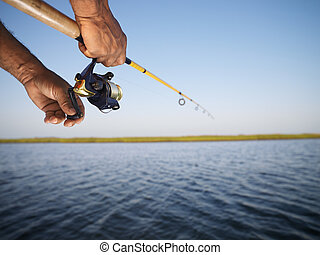 African-American male hand holding fishing rod and reeling the other hand.