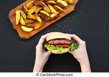 Hands holding fresh burger. Fried potatoes on wooden board. Top view.