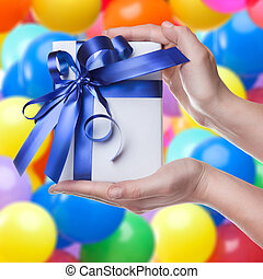 Hands holding gift in package with blue ribbon