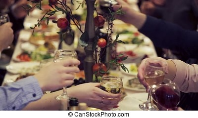 Hands holding glasses and toasting, happy festive moment, luxury celebration concept. Clink of glasses at the festive table. People clink glasses together. Guest toasting with glasses at luxury wedding reception