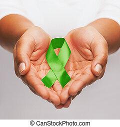 hands holding green awareness ribbon
